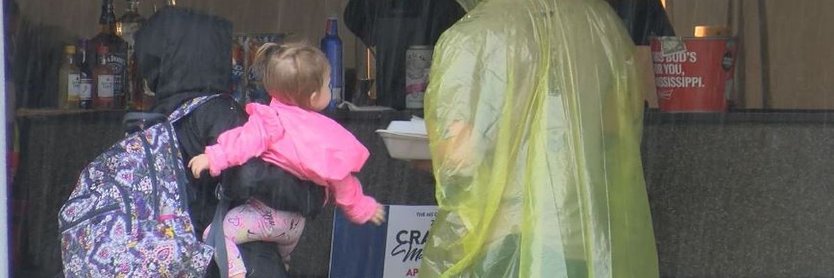 Vendors, visitors slogging through wet Crawfish Festival