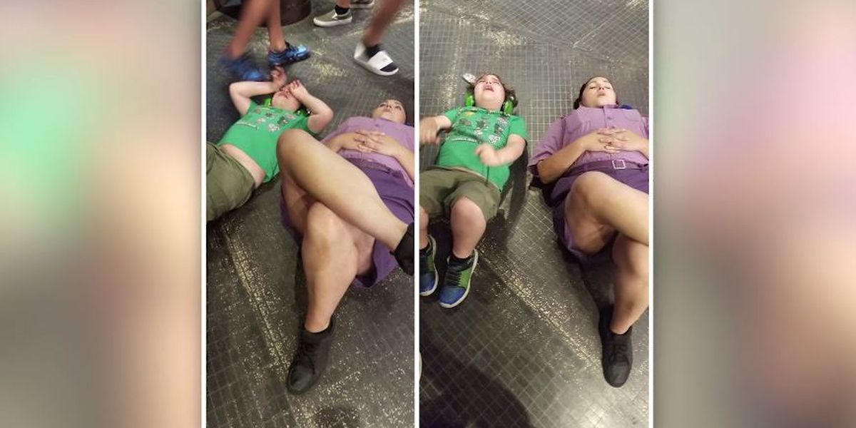 Theme park worker helps calm boy with autism by lying on floor with him during meltdown