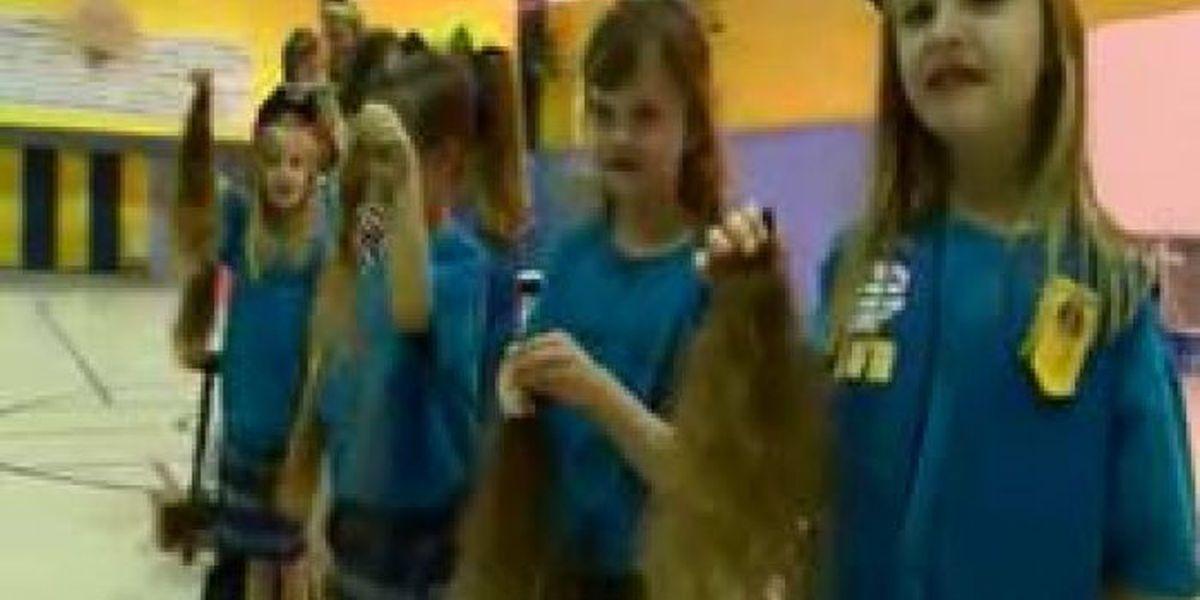 Students cut teacher's hair for a cause